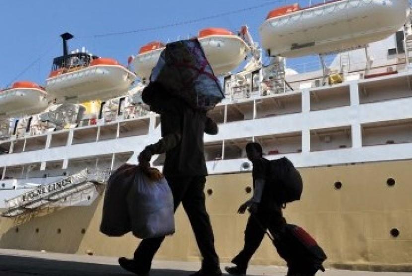Dua calon penumpang mengangkat barangnya saat akan naik ke KM Labobar di Pelabuhan Soekarno-Hatta Makassar, Sulsel.