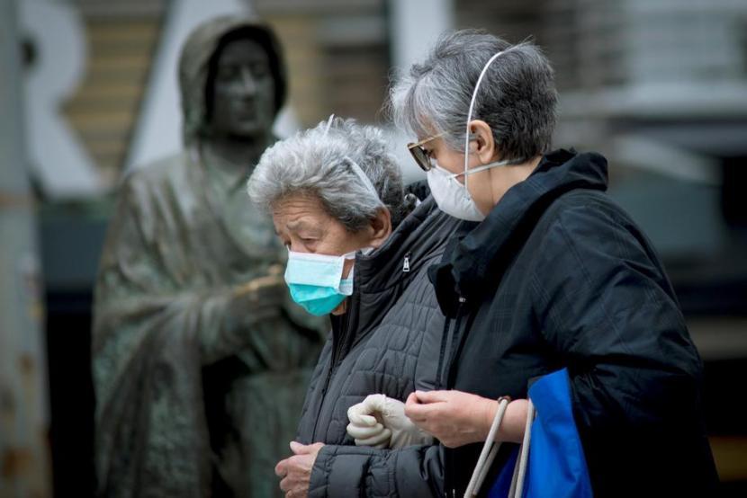 Dua manula berjalan mengenakan masker di Ourense, sebelah barat laut Spanyol, pada Sabtu (21/3). Angka kematian Spanyol akibat covid-19 telah melampaui China.