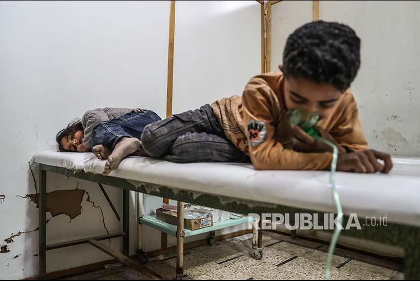 Dua orang anak memperoleh penanganan medis setelah terpapar gas beracun di Desa Shifunieh, Ghouta Timur, Suriah, Ahad (25/2).