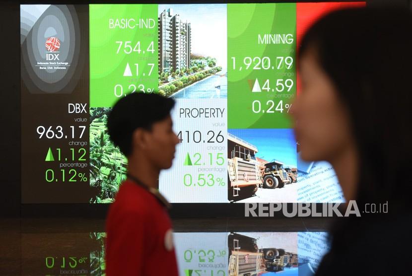 Dua orang melintasi layar elektronik pergerakan saham di Bursa Efek Indonesia, Jakarta, Jumat (19/10/2018).