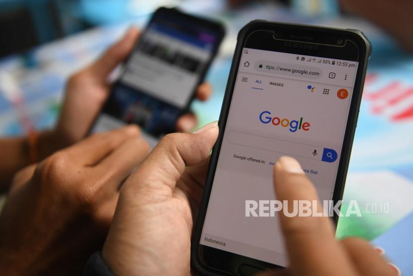 Dua orang membuka laman Google dan aplikasi Facebook melalui gawainya di Jakarta, Jumat (12/4/2019).