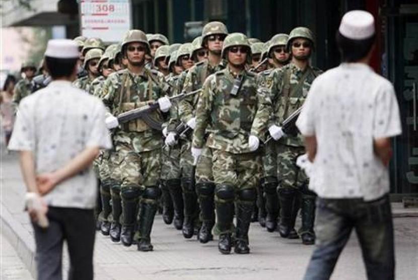 Dua orang Muslim Uighur di Xinjiang melintas di depan parade militer Cina.