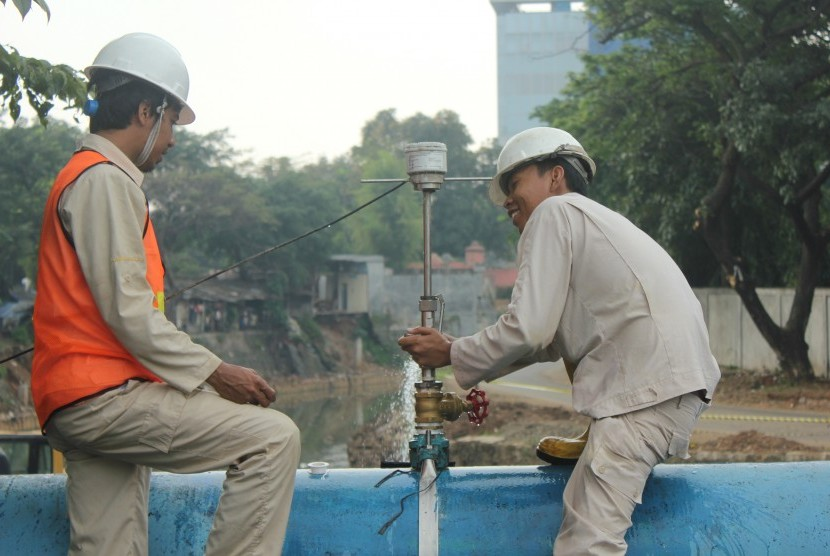 Dua orang petugas PT PAM Lyonnaise Jaya (Palyja) tengah memasang alat ukur aliran air air (flow meter) di boundary pipe Jalan Diponegoro, Jakarta Pusat, Selasa (6/8).