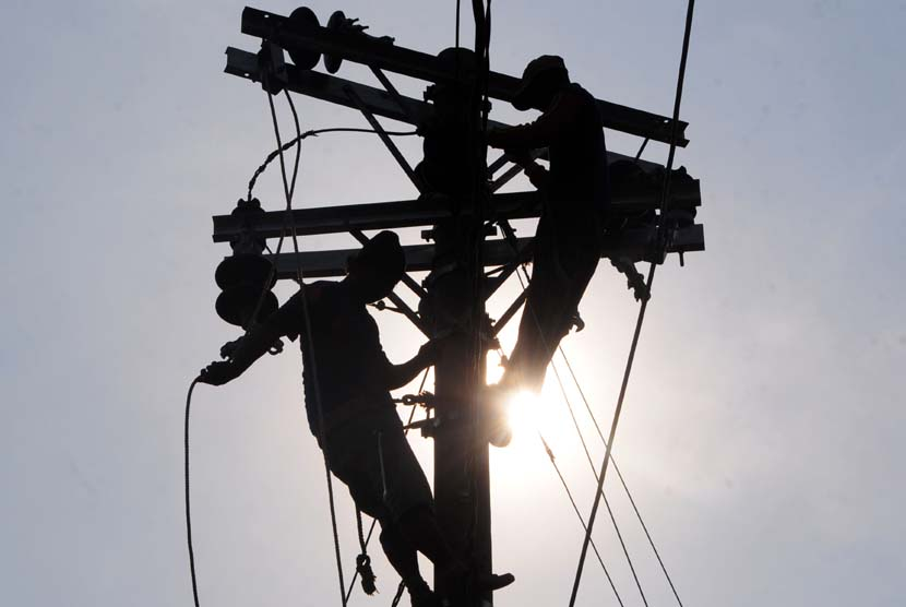 Dua pekerja memperbaiki instalasi listrik (ilustrasi).