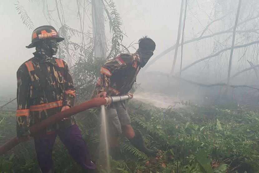 Dua pemadam kebakaran Kapuas Bhakti Pontianak menyemprotkan air ke hutan yang terbakar di belakang perumahan Residence Borneo Khatulistiwa di Sungai Raya, Kabupaten Kubu Raya, Kalbar, Sabtu (18/8).