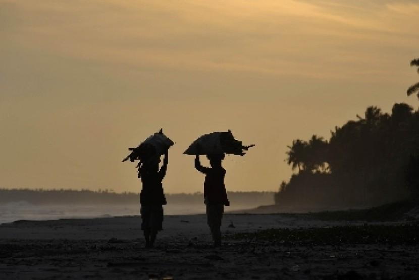 Dua pencari kayu bakar berjalan di pinggir pantai Tanjung Setia, Krui, Lampung Barat, Lampung, Jumat (29/7). Tanjung Setia menjadi salah satu potensi wisata unggulan Lampung dengan ombak yang baik bagi peselancar dan pemandangan yang indah bagi wisatawan p