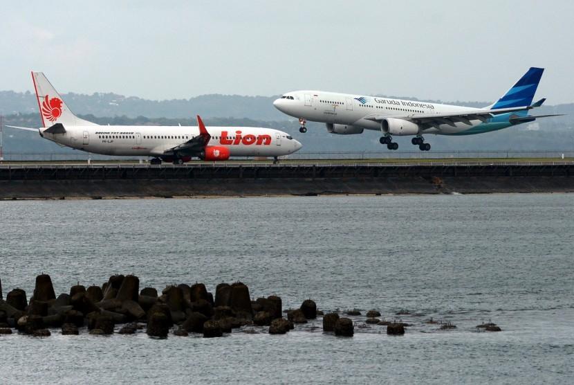 Dua pesawat terbang dan mendarat di landasan pacu Bandara Ngurah Rai, Bali, Senin (19/6).