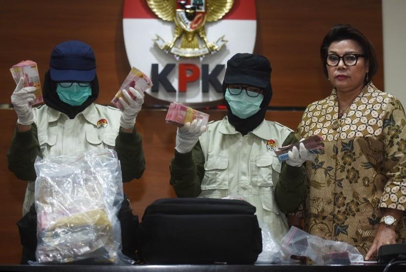 Dua petugas disaksikan Wakil Ketua KPK Basaria Panjaitan (kanan) menunjukkan barang bukti uang yang diamankan dari operasi tangkap tangan (OTT) Nganjuk, di Jakarta, Kamis (26/10).