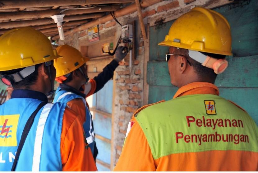 Dua petugas PLN memasang instalasi sambungan listrik secara gratis untuk warga tidak mampu di Kampung Panenjoan, Carenang, Serang, Banten, Jumat (13/7).