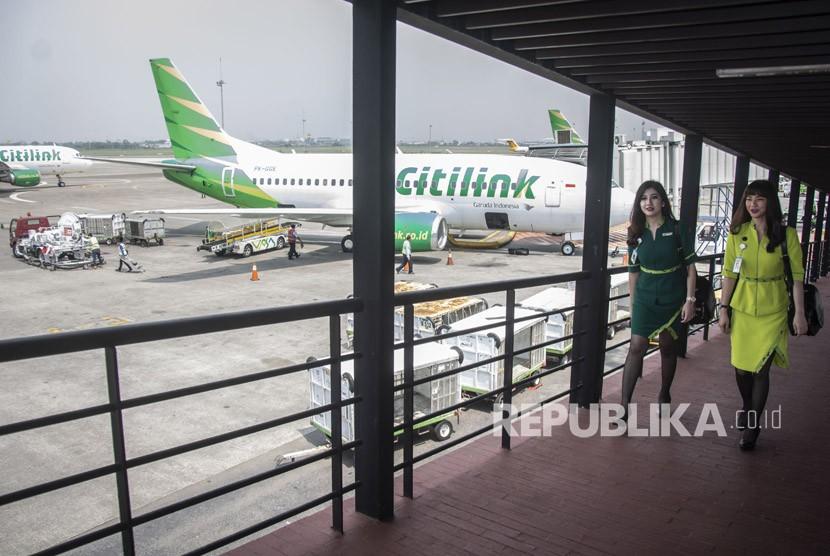 Dua pramugari maskapai Citilink Indonesia dengan menggunakan seragam baru berjalan di samping pesawat Citilink sebelum mengikuti penerbangan perdana seragam baru Citilink Indonesia rute Jakarta-Surabaya di Bandara Internsional Soekarno-Hatta, Tangerang, Banten.