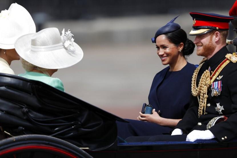 Duchess of Sussex Meghan Markle dan Pangeran Harry duduk di kereta kuda saat menghadiri parade militer tahunan ulang tahun Ratu Elizabeth II, Sabtu (8/6).