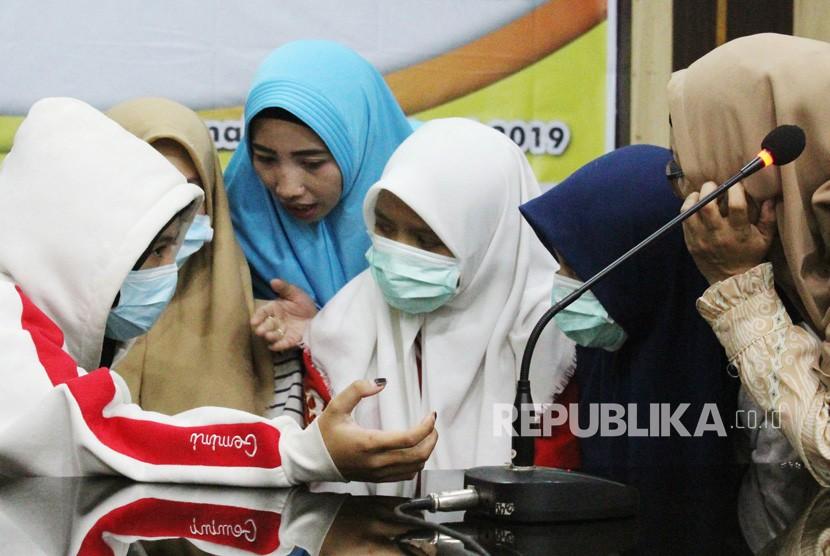 Empat dari 12 siswi SMU yang diduga menjadi pelaku dan saksi dalam kasus penganiayaan siswi SMP berinisial AU (14) berdiskusi dengan kerabat di sela jumpa pers yang digelar di Mapolresta Pontianak, Kalimantan Barat, Rabu (10/4/2019).