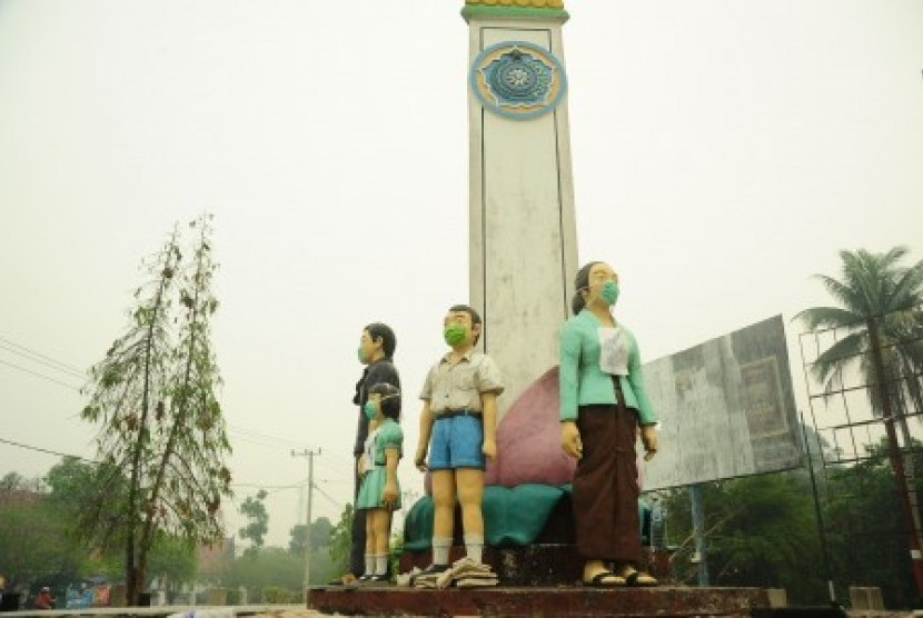 Empat patung Keluarga Berencana (KB) mengenakan masker di Jalan S Parman, Palangkaraya, Kalteng, Selasa (27/10). Masker tersebut dipasang oleh warga setempat, sebagai aksi protes terhadap pemerintah daerah yang dinilai lamban dalam menangani bencana asap d