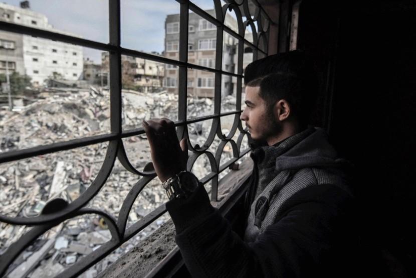 Fadi memandangi puing-puing rumah yang hancur akibat serangan Israel dari rumahnya di Apartemen Al Rahma, Gaza.