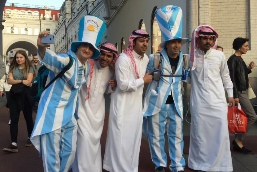 Fan Arab Saudi mengenakan pakaian khas pria Timur Tengah, berfoto bersama fan Argentina jelang kick-off perdana Piala Dunia 2018 di Stadion Luzhniki, Moskow, Kamis (14/6) malam WIB.
