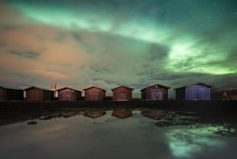 Fenomena alam aurora borealis atau northern lights tampak di langit dekat Reykjanesbaer di Islandia, (14/10).