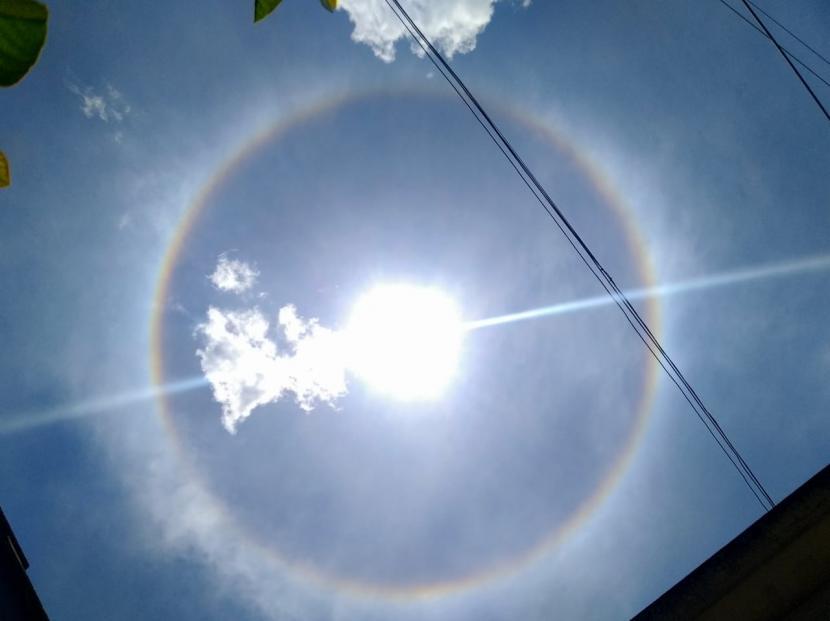 Fenomena lingkaran cahaya yang mengelilingi matahari terlihat jelas oleh mata di Kota Bandung dan sekitarnya, Senin (22/3) siang. Diketahui bahwa lingkaran cahaya di sekitar matahari atau juga yang bisa terdapat di bulan tersebut atau fenomena optis disebut Halo.