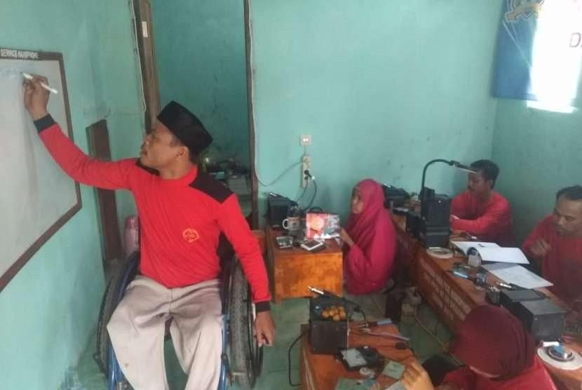 Ferdy Syamsuddin memberikan pelatihan memperbaki telepon genggam ke penyandang disabilitas yang lain.