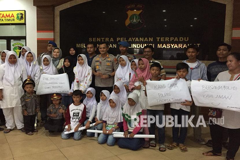 Forum Anak Cakung bersama perwakilan KPAI, berikan bunga kepada anggota polisi di Polres Metro Jakarta Timur, kepada Wakapolres Metro Jakarta Timur mereka meminta agar polisi melindungi anak-anak dari doktrin terorisme, Sabtu (19/5).