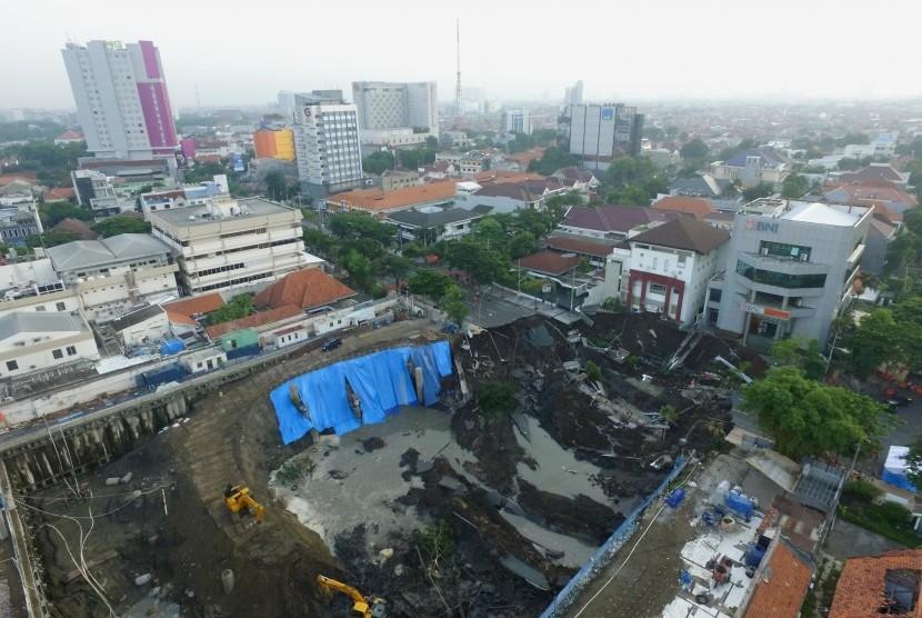 Foto aerial kondisi tanah ambles di Jalan Raya Gubeng, Surabaya, Jawa Timur, Rabu (19/12/2018). Jalan raya tersebut ambles sedalam sekitar 20 meter dengan lebar 30 meter pada Selasa (18/12/2018) malam diduga karena proyek pembangunan gedung di sekitar lokasi.