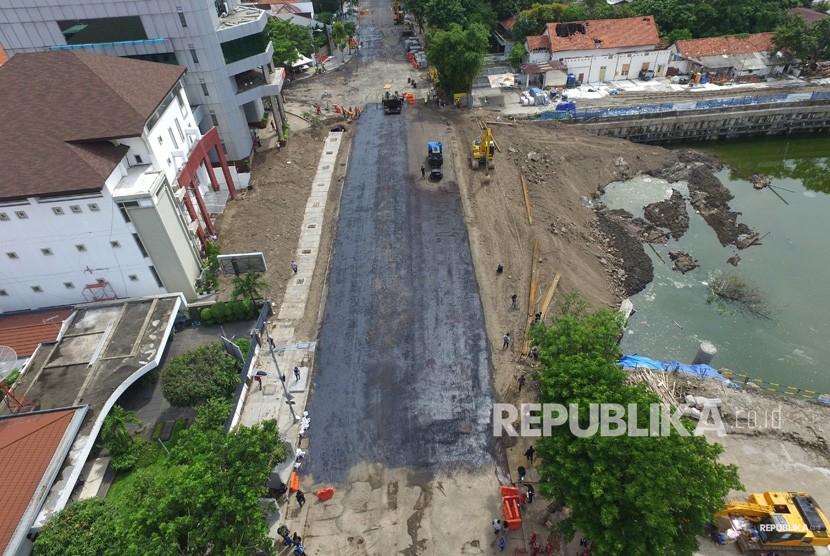 Foto aerial pekerja melakukan proses 'prime coat' pada urukan tanah sebelum diaspal di lokasi jalan ambles di Jalan Raya Gubeng, Surabaya, Jawa Timur, Rabu (26/12/2018).