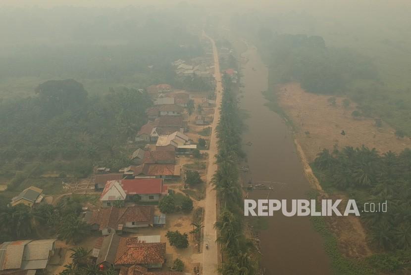 Foto udara kawasan permukiman penduduk yang diselimuti kabut asap di Arang-arang, Kumpeh Ulu, Muarojambi, Jambi, Kamis (15/8/2019).