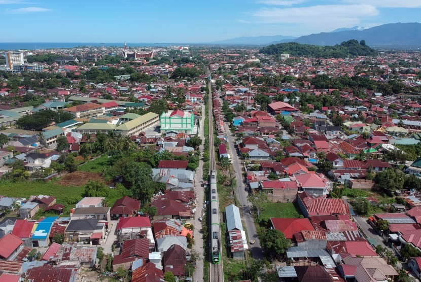 Foto udara Kereta Api (KA) Bandara Internasional Minangkabau (BIM), Minangkabau Ekspres, melintas di antara permukiman di Kota Padang, Sumatera Barat, Rabu (13/3/2019).