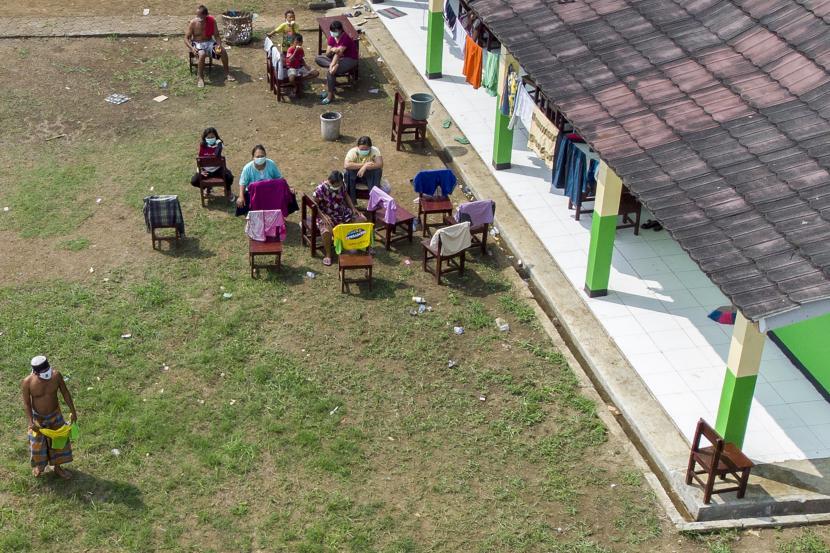 Foto udara sejumlah pasien COVID-19 berjemur saat menjalani isolasi mandiri di Madrasah Birrul Walidain, Rengasdengklok, Karawang, Jawa Barat, Selasa (8/6/2021). Sebanyak 28 orang terkonfirmasi positif COVID-19 yang berasal dari klaster mudik dan klaster wisata dirawat di ruang isolasi mandiri swadaya masyarakat tersebut guna mengantisipasi penularan COVID-19.