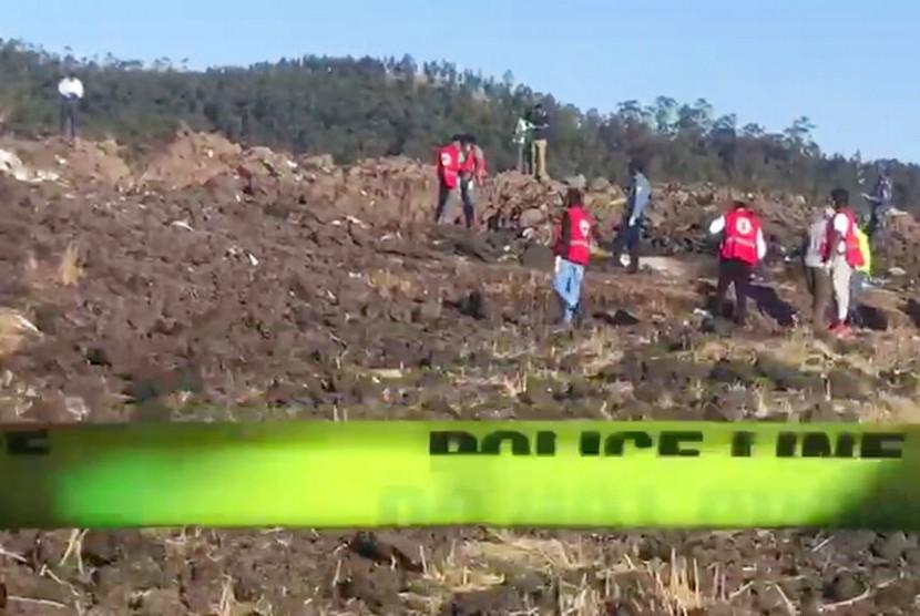 Foto yang diambil dari video menunjukkan petugas mencari korban diantara puing-puing jatuhnya pesawat Ethiopian Airlines di daerah Hejere sekitar 50 km dari selatan Addis Ababa Kenya, Ahad (10/3).