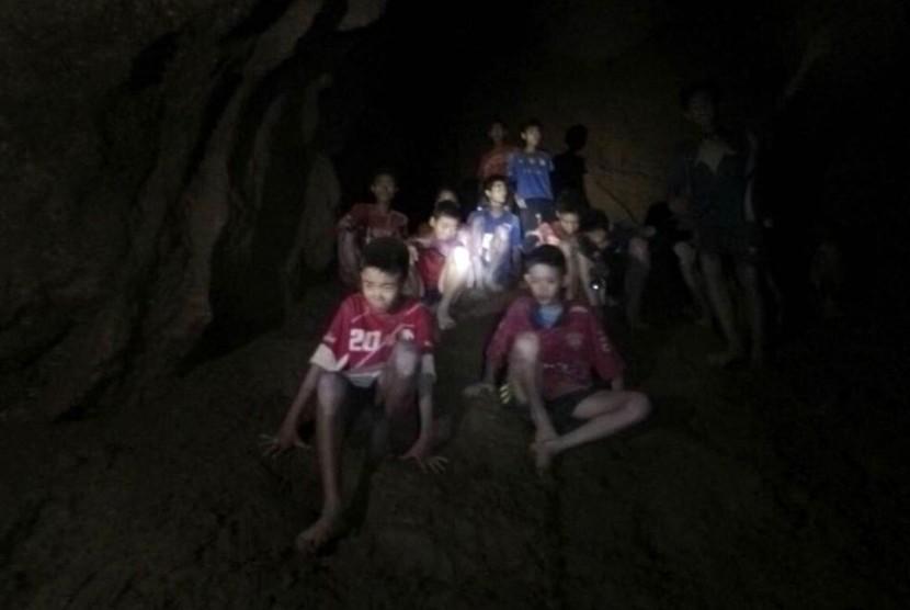 Foto yang dirilis Tham Luang Rescue Operation Center menunjukkan tim sepak bola remaja Thailand dan pelatihnya saat ditemukan di dalam gua yang setengah terendam banjir di Mae Sai, Chiang Rai, Thailand, Senin (2/7).