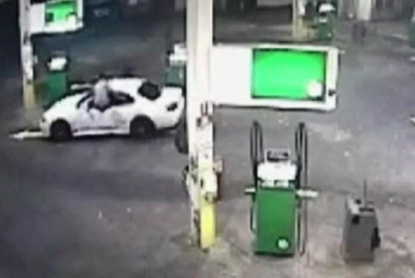 Gambar dari CCTV yang menunjukkan si pemilik mobil lompat masuk ke dalam jendela mobil untuk menghalau pencuri yang membawa mobilnya.