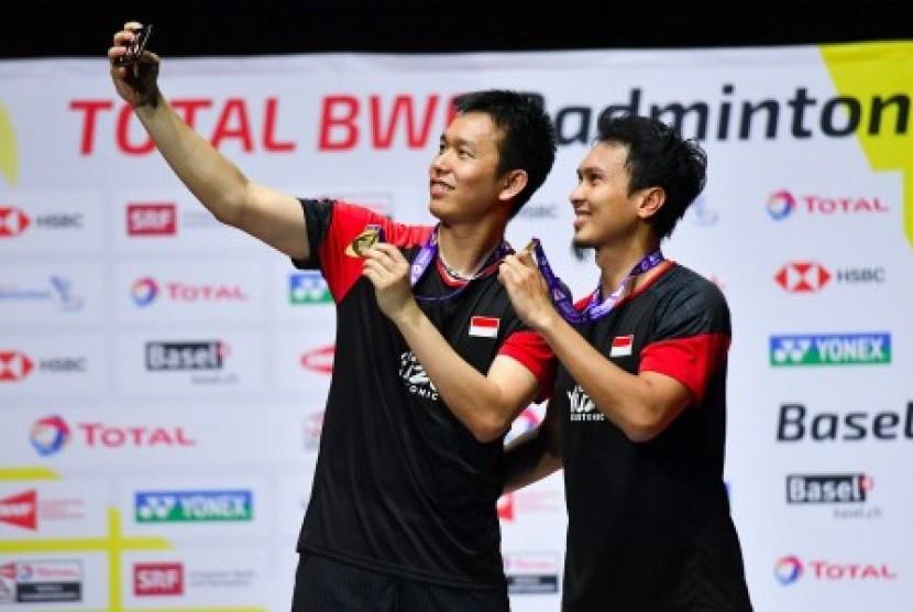 Ganda putra Indonesia Hendra Setiawan (kiri) dan Mohammad Ahsan berswafoto dengan menunjukan medali emas saat prosesi penyerahan medali pada Kejuaraan Dunia Bulu Tangkis 2019 di St. Jakobshalle, Basel, Swiss, Ahad (25/8/2019).