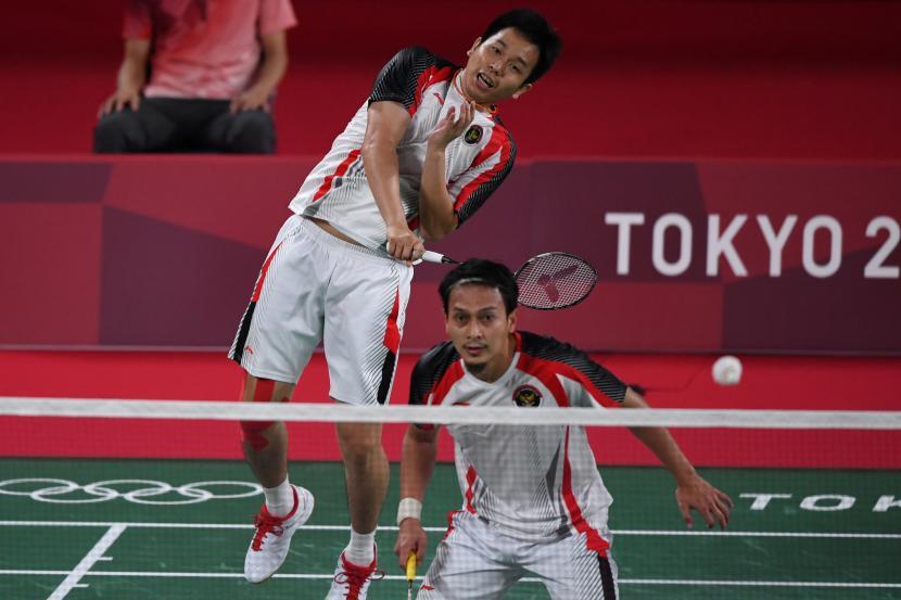 Ganda putra Indonesia Hendra Setiawan (kiri) dan Mohammad Ahsan mengembalikan kok ke arah ganda putra Korea Solgyu Choi dan Seungjae Seo dalam penyisihan Grup D Olimpiade Tokyo 2020 di Musashino Forest Sport Plaza, Tokyo, Jepang, Selasa (27/7/2021). Ahsan dan Hendra berhasil menjadi juara grup D setelah menang 21-12, 19-21, 21-18 atas Solgyu Choi dan Seungjae Seo.