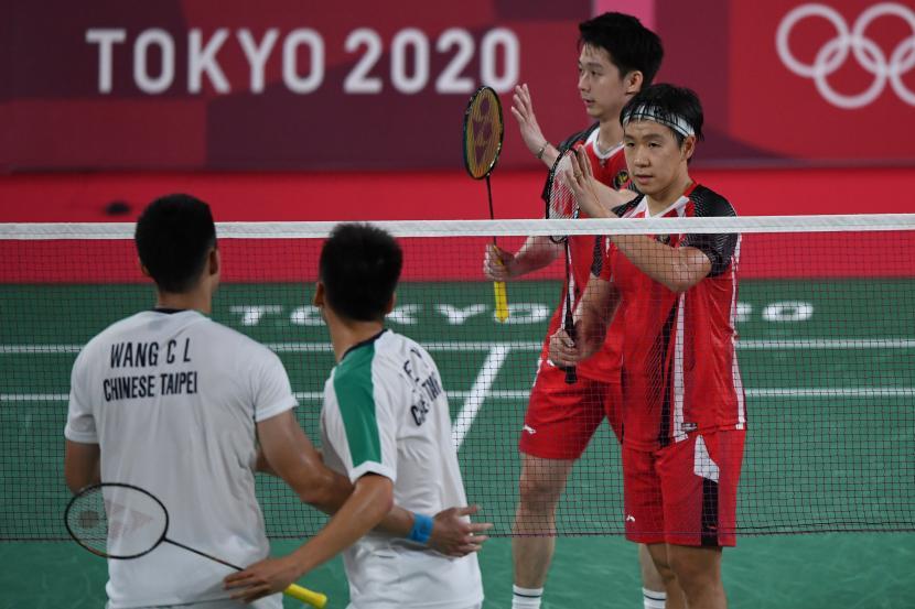 Ganda putra Indonesia Marcus Fernaldi Gideon (kanan) dan Kevin Sanjaya Sukamuljo (kedua kanan) memberikan ucapan selamat kepada ganda putra Taiwan, Yang Lee/Chi-Lin Wang, seusai penyisihan Grup A Olimpiade Tokyo 2020 di Musashino Forest Sport Plaza, Tokyo, Jepang, Selasa (27/7/2021). Marcus dan Kevin kalah 18-21, 21-15, 17-21 dari ganda putra Taiwan.