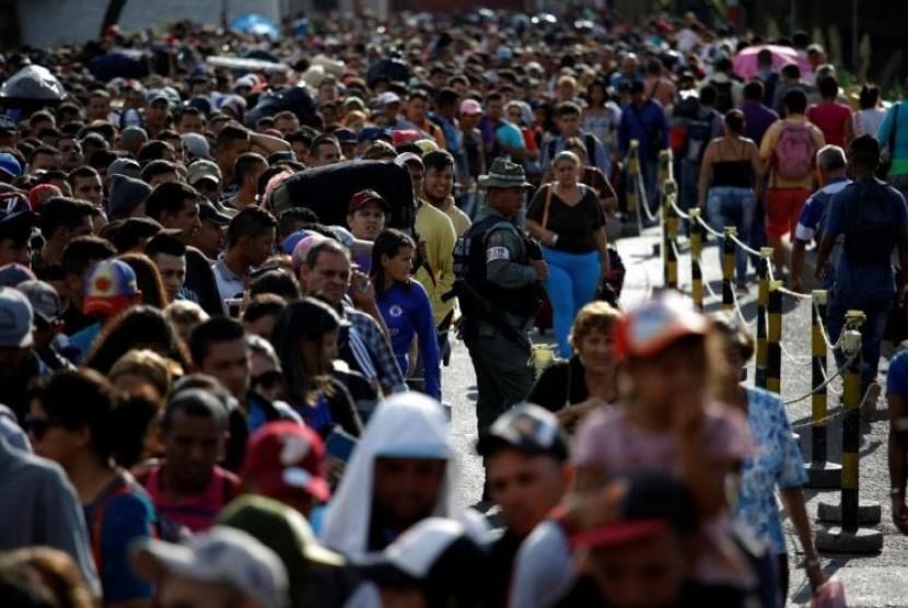 Garda Nasional Venezuela mengawasi warga yang mengantre untuk menyeberang dari Venezuela menuju Kolombia.