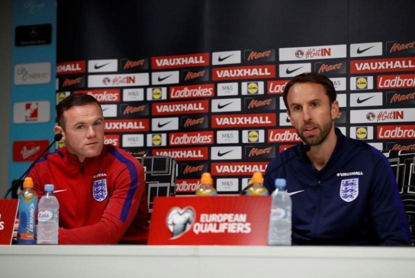 Gareth Southgate (kanan) dan Wayne Rooney dalam konferensi pers timnas Inggris, Senin (10/10).
