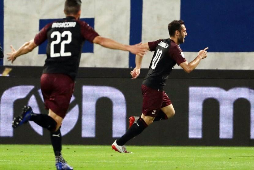 Gelandang AC Milan Hakan Calhanoglu (kanan) merayakan golnya ke gawang SPAL.