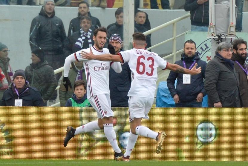 Gelandang AC Milan Hakan Calhanoglu (kiri) merayakan golnya ke gawang Fiorentina bersama rekan setimnya, Patrick Cutrone (kanan) di Stadion Artemio Franchi, Florence, Sabtu (30/12). Milan bermain imbang 1-1 di markas Fiorentina.
