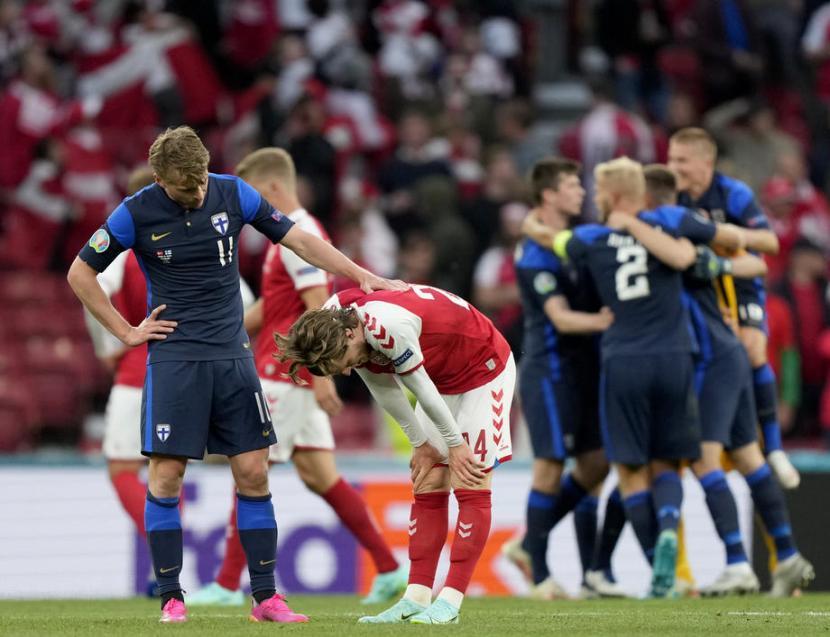 Gelandang Finlandia, Rasmus Schuller (kiri) menenangkan gelandang Denmark, Mathias Jensen yang terlihat kecewa seusai laga kualifikasi Grup B Piala Eropa 2020 di Stadion Parken, Kopenhagen, Ahad (13/6). Finlandia menang 1-0.