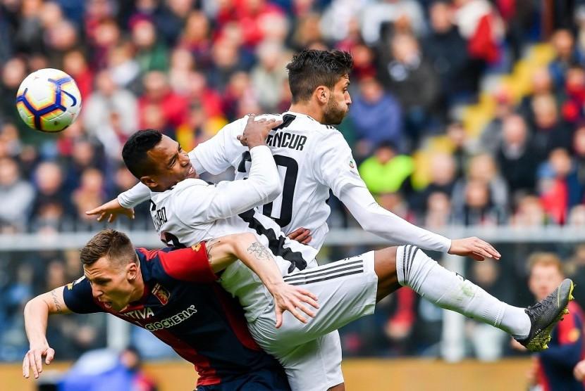 Gelandang Genoa Lukas Lerager (kiri) berebut bola dengan pemain Juventus Alex Sandro (tengah) dan Rodrigo Bentancur dalam laga pekan ke-28 Serie A di Stadion Luigi Ferraris, Genoa, Ahad (17/3).