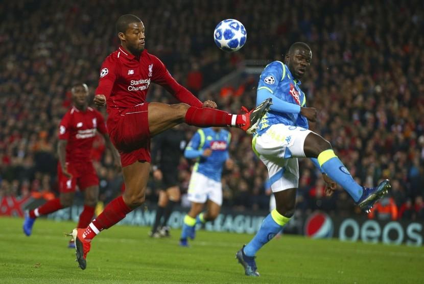 Gelandang Liverpool Georginio Wijnaldum dibayangi bek Napoli Kalidou Koulibaly (kanan) pada laga Grup C Liga Champions antara Liverpool melawan Napoli  di stadion Anfield, Liverpool, (12/12) dini hari.
