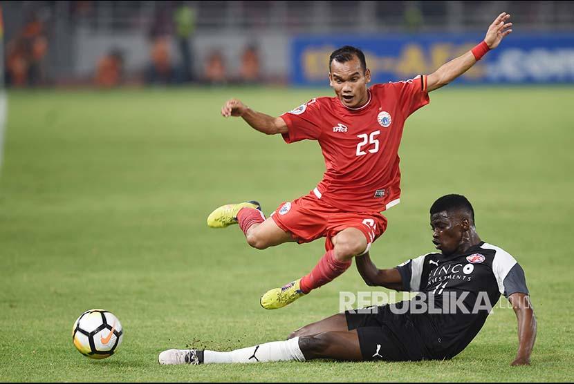 Gelandang Persija Jakarta Riko Simanjuntak (atas) mencoba melewati hadangan pesepak bola Home United Sirina Camara (bawah)