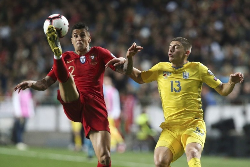 Gelandang Portugal Joao Cancelo (kiri) berebut bola dengan pemain Ukraina Vitaliy Mykolenko dalam laga kualifikasi Piala Eropa 2020.