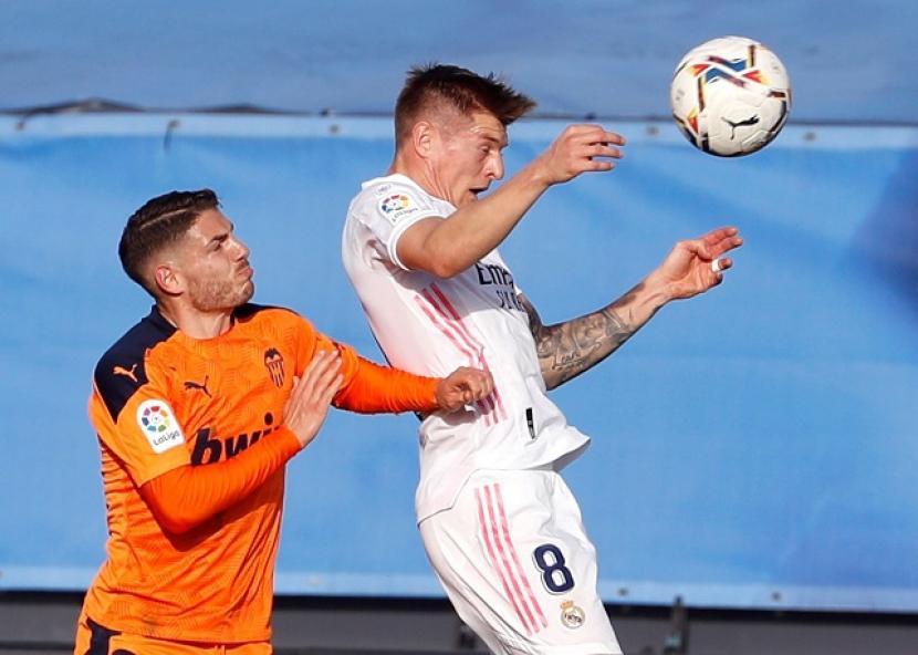 Gelandang Real Madrid Toni Kroos menanduk bola dalam pertandingan La Liga Spanyol melawan Valencia.