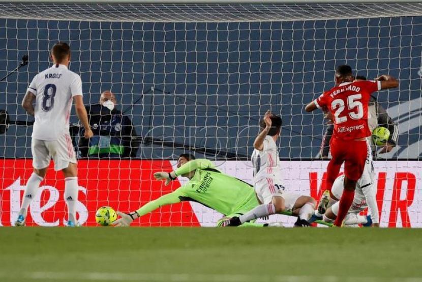 Gelandang Sevilla Fernando Reges (merah) mencetak gol ke gawang Real Madrid.