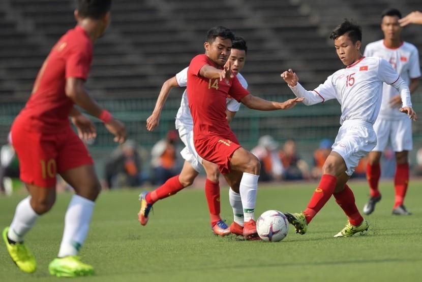 Gelandang timnas Indonesia U-22 Asnawi Mangkualam (tengah) berebut bola dengan pemain Vietnam U-22 pada semifinal Piala AFF U-22, Ahad (24/2).