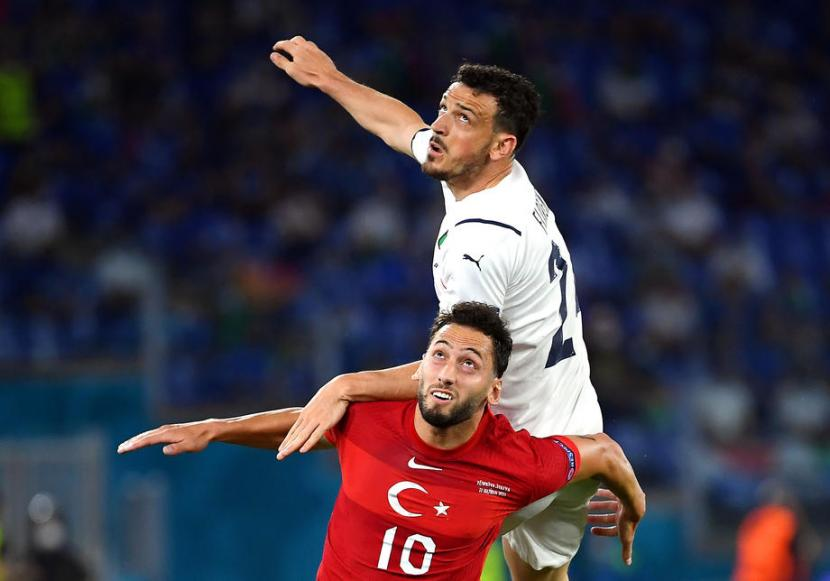Gelandang Timnas Turki, Hakan Calhanoglu (bawah), berebut bola dengan pemain Itali, Alessandro Florenzi, dalam laga Grup A Euro 2020 di Stadion Olimpico, Roma, Jumat (11/6).