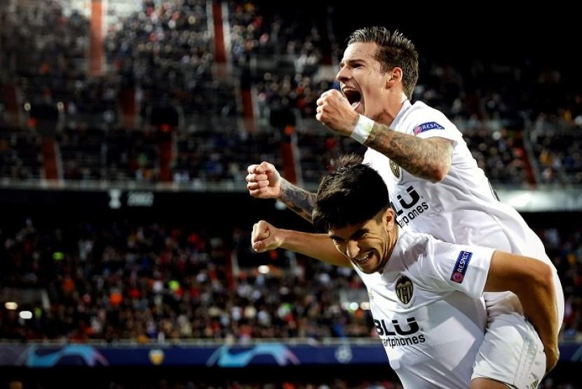 Gelandang Valencia Carlos Soler (bawah) merayakan gol yang dicetaknya ke gawang BSC Young Boys bersama rekannya Santi Mina.
