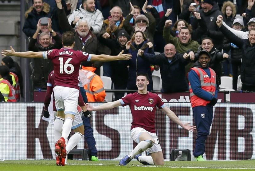 Gelandang West Ham United, Declan Rice (kanan), merayakan golnya ke gawang Arsenal.