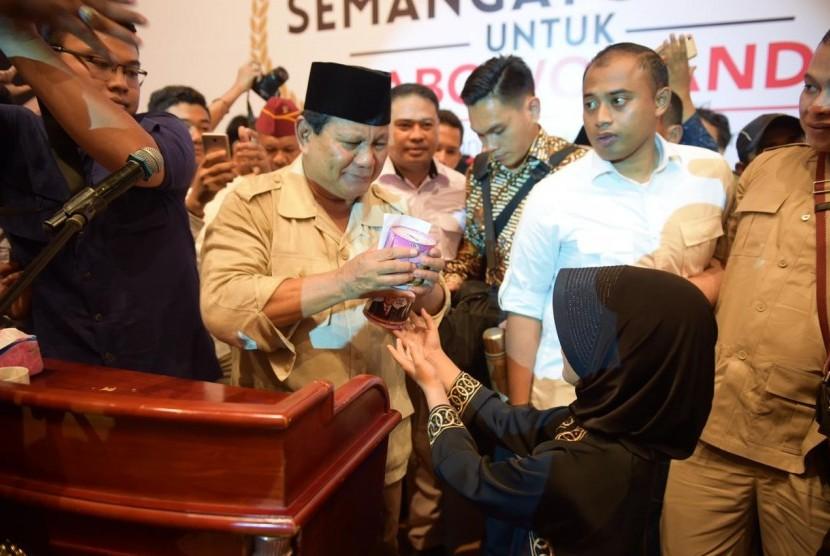 Gendis  (kerudung hitam) menyerahkan tabungan kepada Prabowo di Medan (23/2).